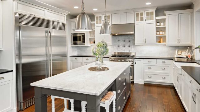 Renovated kitchen with chrome appliances and cabinet handles