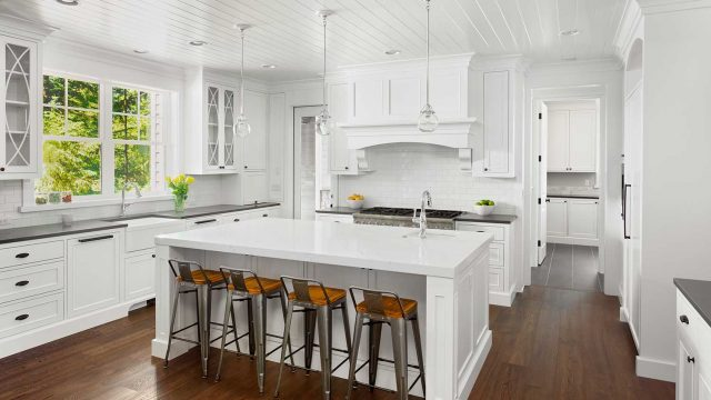 All-white kitchen with crown molding and subway tile